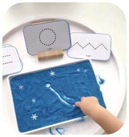 criança desenha formas simples em caixa de areia azul