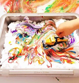 criança brinca com carrinho em chantilly colorido