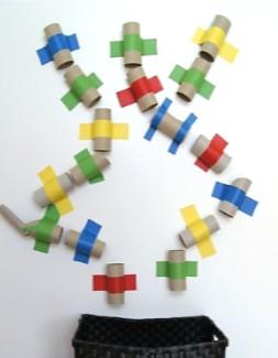 canudos de papel colados com fita cola numa parede e dispostos num percurso (para pequenos objetos) que termina num cesto grande no chão