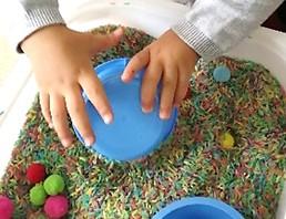 criança manuseia arroz e bolinhas de feltro coloridas dentro de um alguidar.